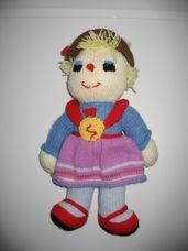 Rövid szőke hajú horgolt kalapos lány piros-kék-lila ruhában