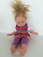 Puha törzsű kék szemű szőke hajú kislány baba lila ruhában