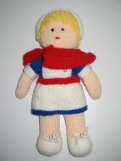 Nővérke ruhás szőke hajú baba piros vállkendővel