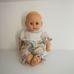 Szépséghibás baba pasztellszínű fodros overálban
