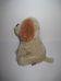 Hátsó lábain ülő drappbarna plüss kutya világosbarna füllel
