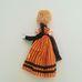 Retró népviseletes ruhát viselő szőke göndör hajú baba